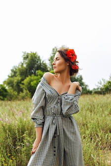 Portrait of a beautiful brunette woman in dress with red flowers in her hair in the field