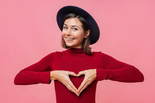 Portrait of beautiful brunette woman in hat , shows heart gesture over chest, being passionate, express love to close person, stands.