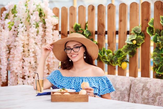 Portrait of beautiful brunette woman having lunch in the outdoor cafe veranda in summer.