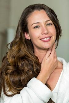 Portrait of beautiful brunette woman smiling in bathroom