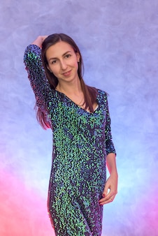 Portrait of beautiful brunette woman in sparkling evening dress