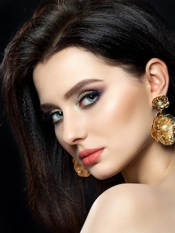 Portrait of beautiful brunette woman with golden earrings. shiny multicolor smokey eyes. luxury skincare and modern fashion makeup concept.