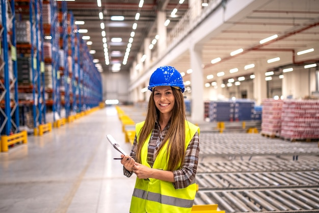 Portrait of beautiful brunette woman with hardhat and reflective jacket holding checklist in big warehouse storage area
