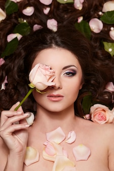 Portrait of beautiful brunette woman with long curly hair and bright makeup witjh flowers in hair