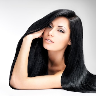 Portrait of a beautiful brunette woman with long straight hair poses at grey