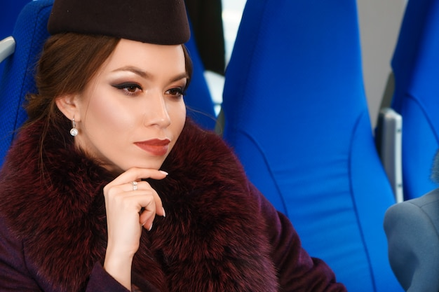 Portrait of a beautiful brunette woman with makeup in a train car
