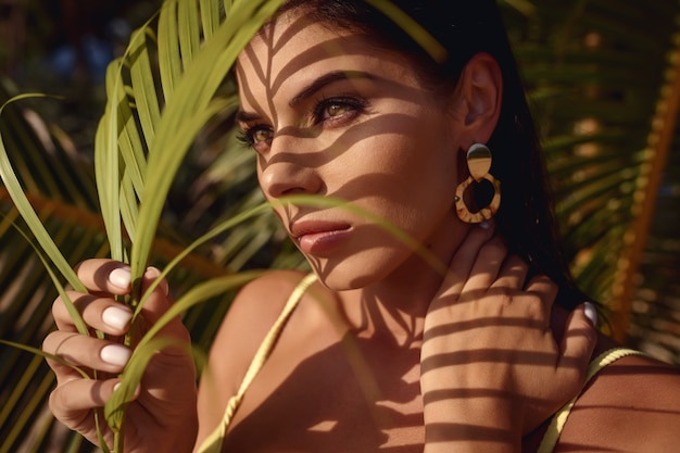 Portrait of a beautiful brunette woman with palm leaf shadows on her face