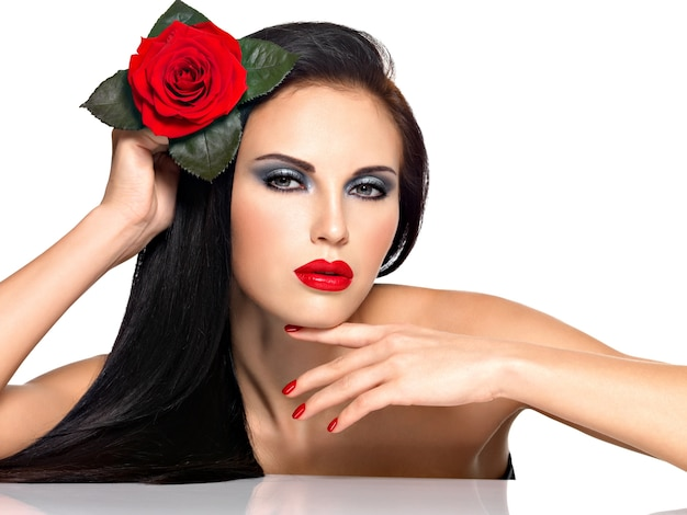 Portrait of a beautiful brunette woman with red nails and lips holds the red rose