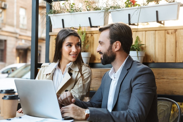 Portrait of beautiful business couple man and woman in formal wear having conversation and working on laptop together while sitting in cafe outdoors