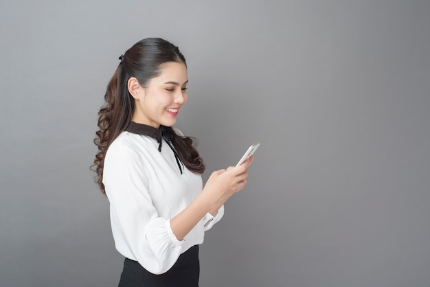 Portrait of beautiful business woman is using cellphone in studio