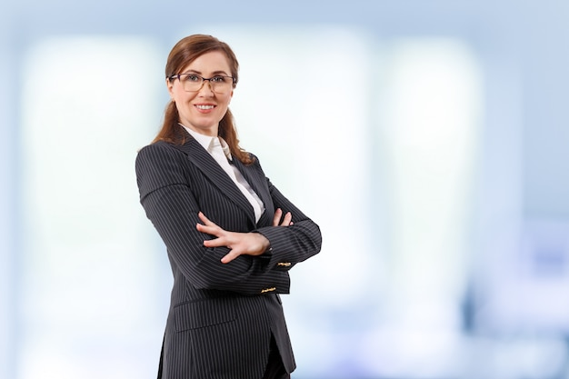 Portrait of a beautiful businesswoman 50 ears old in crossed arms pose in the office.