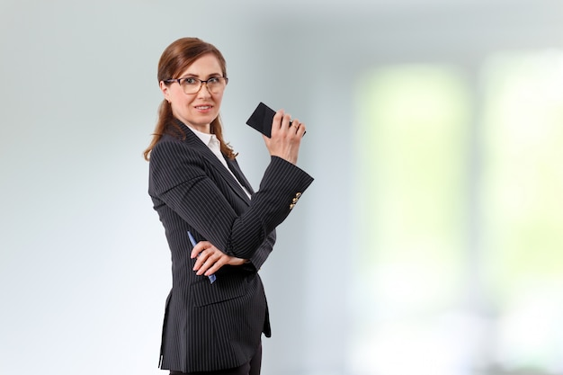 Portrait of a beautiful businesswoman 50 ears old with mobile phone in the office.