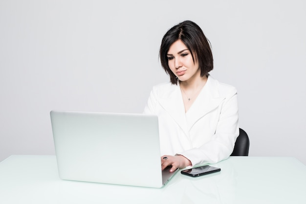 Ritratto di una bella donna d'affari seduta alla scrivania che lavora isolata su grigio