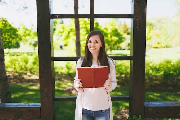 Portrait of beautiful calm peaceful young woman wearing light casual clothes, jeans, relaxing, reading book. smiling female resting in city park in street outdoors on spring nature. lifestyle concept.