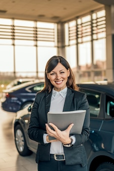 Portrait of beautiful car saleswoman.