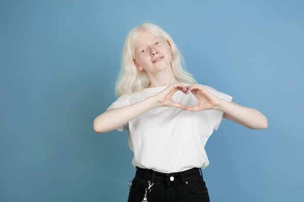 Portrait of beautiful caucasian albino girl isolated on blue  wall