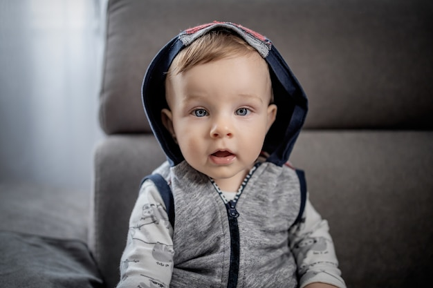 Portrait of beautiful caucasian baby boy with big blue eyes with hoodie on head sitting on gray couch.