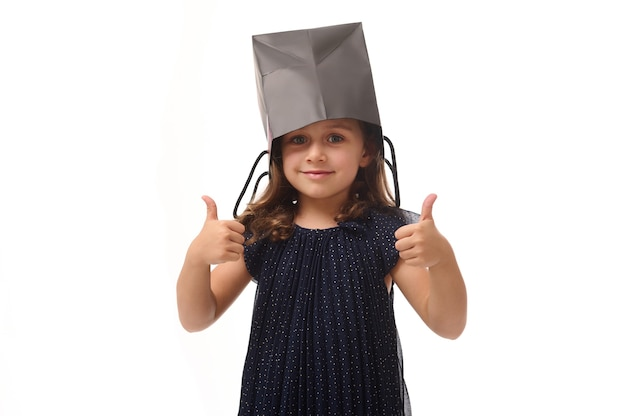 Portrait of beautiful caucasian baby girl having fun, putting a black shopping packet on her head, looking at camera, showing thumbs up with her fingers. black friday concept