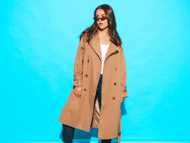 Portrait of beautiful caucasian brunette woman model in brown overcoat and sunglasses.girl posing near blue wall