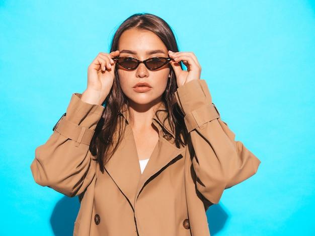 Ritratto di bello modello caucasico della donna del brunette in cappotto ed occhiali da sole marroni. ragazza che posa vicino alla parete blu