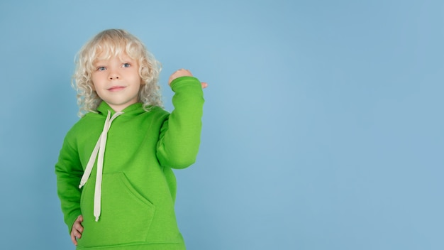Portrait of beautiful caucasian little boy isolated on blue studio background. blonde curly male model. concept of facial expression, human emotions, childhood, ad, sales.
