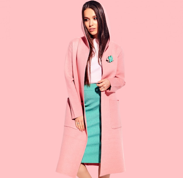Portrait of beautiful caucasian smiling brunette woman model in bright overcoat and summer stylish skirt posing  on pink background