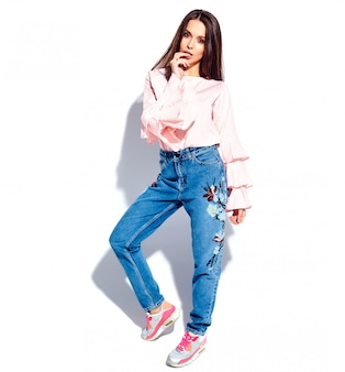 Portrait of beautiful caucasian smiling brunette woman model in bright pink blouse and summer stylish blue jeans with flowers print