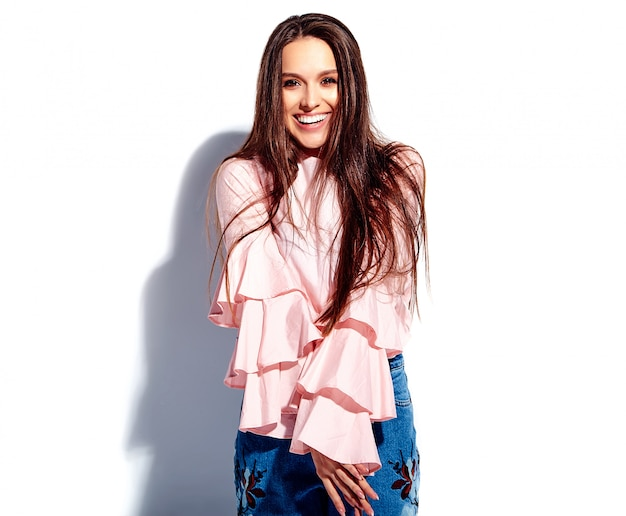 Portrait of beautiful caucasian smiling brunette woman model in bright pink blouse and summer stylish blue jeans with flowers