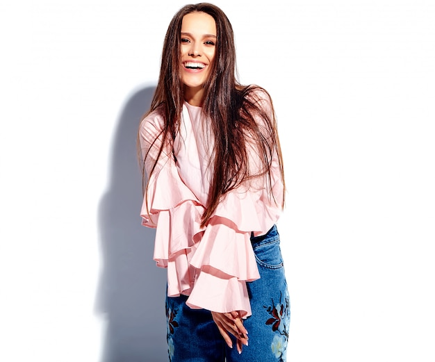 Portrait of beautiful caucasian smiling brunette woman model in bright pink blouse and summer stylish blue jeans