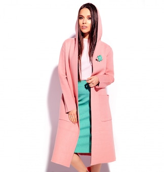 Portrait of beautiful caucasian smiling brunette woman model in bright pink overcoat and summer stylish blue skirt isolated on white background