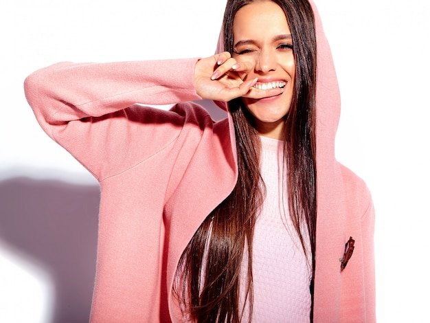 Portrait of beautiful caucasian smiling brunette woman model in bright pink overcoat and summer stylish blue skirt