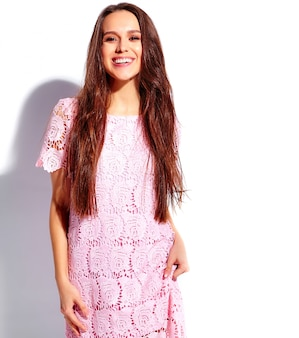 Portrait of beautiful caucasian smiling brunette woman model in bright pink summer stylish dress isolated on white background