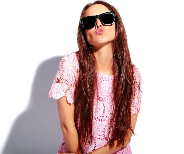Portrait of beautiful caucasian smiling brunette woman model in bright pink summer stylish dress in sunglasses isolated on white background. giving a kiss