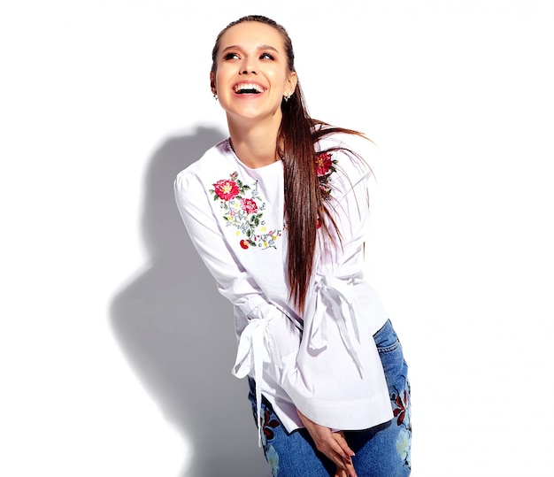 Portrait of beautiful caucasian smiling brunette woman model in white blouse and summer stylish blue jeans with flowers print