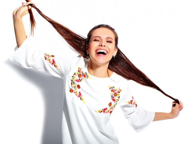 Ritratto di bello modello caucasico sorridente della donna del brunette in vestito alla moda da estate bianca isolato su priorità bassa bianca. torcendosi i capelli