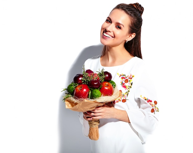 Portrait of beautiful caucasian smiling brunette woman model in white summer stylish dress with unusual creative bouquet of flowers