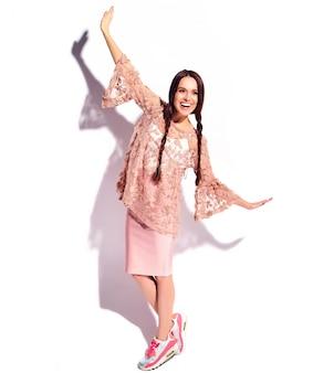 Ritratto di bello modello caucasico sorridente della donna del brunette con le doppie trecce in vestiti alla moda di estate rosa luminosa isolati su priorità bassa bianca. lunghezza intera