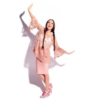 Ritratto di bello modello caucasico sorridente della donna del brunette con le doppie trecce in vestiti alla moda di estate rosa luminosa