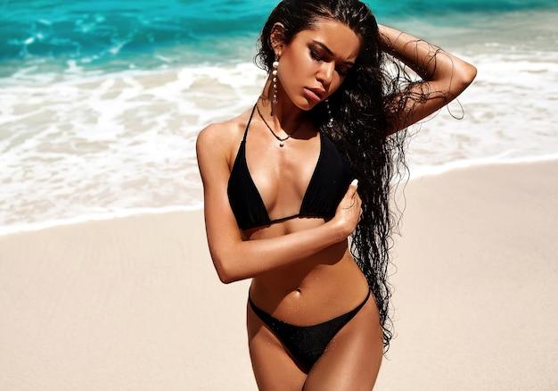 Ritratto di bella donna caucasica modello preso il sole con i capelli lunghi scuri in costume da bagno nero in posa sulla spiaggia estiva vicino al mare blu