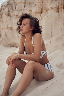 Portrait of beautiful caucasian sunbathed woman model with dark long hair in striped swimsuit lying on summer beach with white sand. top view