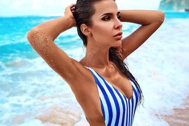 Portrait of beautiful caucasian sunbathed woman model with dark long hair in striped swimsuit posing on summer beach with white sand