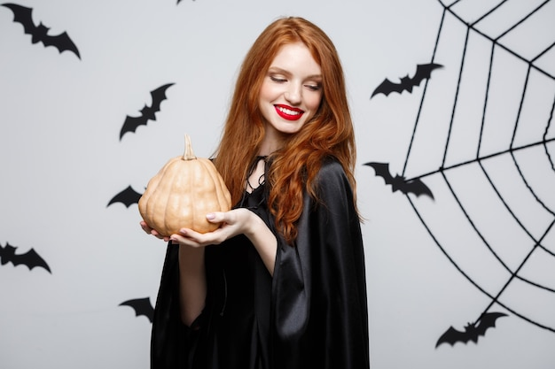 Portrait of beautiful caucasian witch holding pumpkin for celebrating halloween.