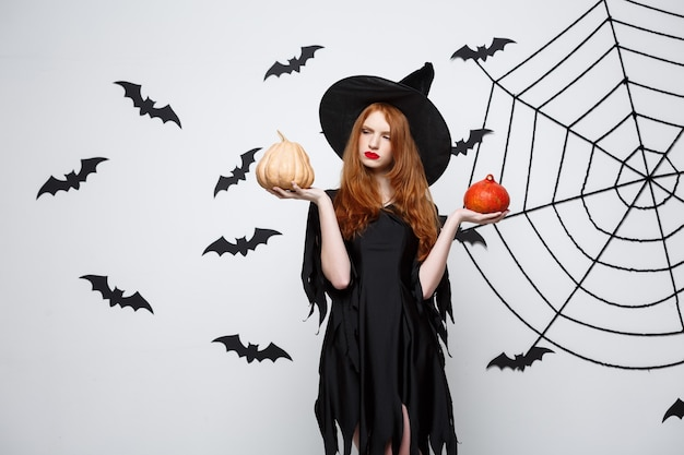 Portrait of beautiful caucasian witch holding pumpkin for celebrating halloween