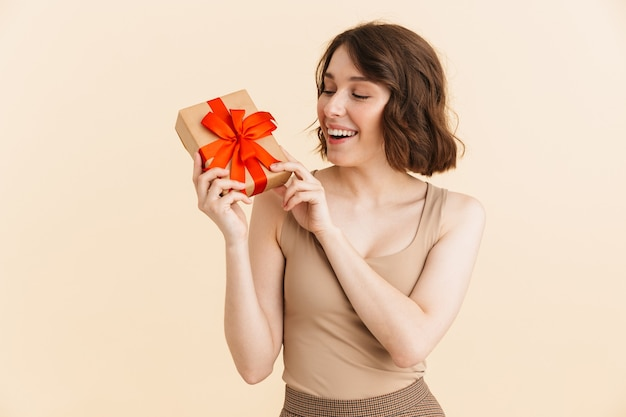 Portrait of beautiful caucasian woman 20s dressed in casual clothes smiling while holding present box isolated