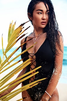 Portrait of beautiful caucasian woman model with dark long hair in black  swimsuit with palm leaf posing on summer beach with white sand on blue sky and ocean