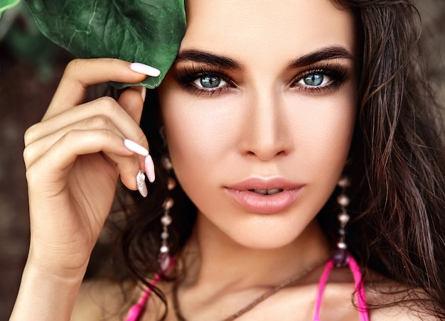 Portrait of beautiful caucasian woman model with dark long hair in pink swimsuit touching green tropical leaf