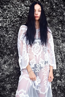 Portrait of beautiful caucasian woman model with dark long hair in transparent white long blouse dress posing near rocks