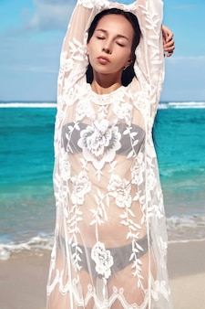 Portrait of beautiful caucasian woman model with dark long hair in transparent white long blouse dress posing on summer beach with white sand on blue sky and ocean