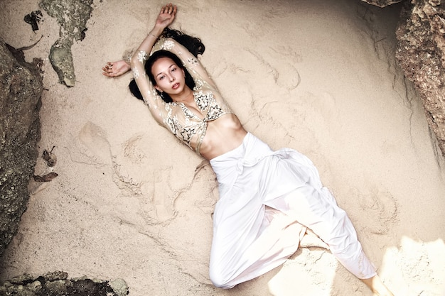 Portrait of beautiful caucasian woman model with dark long hair in wide-leg classic pants  lying on white sand on the beach near rocks. top view