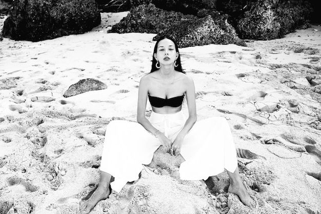 Portrait of beautiful caucasian woman model with dark long hair in wide-leg classic pants sitting on summer beach with white sand near rocks